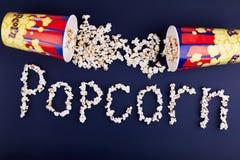 Popcorn λέξης που διασκορπίζεται σε ένα μπλε υπόβαθρο Η έννοια είναι κινηματογράφος Στοκ εικόνες με δικαίωμα ελεύθερης χρήσης