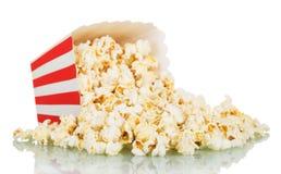 Popcorn που ανατρέπεται από ένα ριγωτό κιβώτιο που απομονώνεται στο λευκό Στοκ εικόνες με δικαίωμα ελεύθερης χρήσης