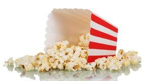 Popcorn που ανατρέπεται το τετραγωνικό ριγωτό κιβώτιο που απομονώνεται από στο λευκό Στοκ Φωτογραφία