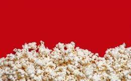 Popcorn που αντιμετωπίζεται άνωθεν στο κόκκινο υπόβαθρο με το διάστημα αντιγράφων Στοκ φωτογραφίες με δικαίωμα ελεύθερης χρήσης