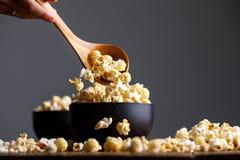 Popcorn πτώσεις από ένα ξύλινο κουτάλι στα φλυτζάνια και γύρω από τα Στοκ Εικόνες