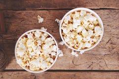Popcorn στα φλυτζάνια εγγράφου στην ξύλινη επιφάνεια Τοπ όψη Στοκ εικόνες με δικαίωμα ελεύθερης χρήσης