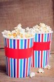 Popcorn στα φλυτζάνια εγγράφου στην ξύλινη επιφάνεια Στοκ Φωτογραφία