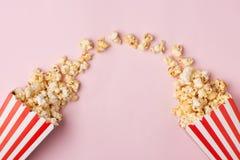 Popcorn στο κόκκινο και άσπρο κουτί από χαρτόνι στο ρόδινο υπόβαθρο Στοκ Εικόνα