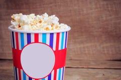 Popcorn στο φλυτζάνι εγγράφου στην ξύλινη επιφάνεια διάστημα αντιγράφων Στοκ Εικόνες