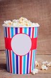 Popcorn στο φλυτζάνι εγγράφου στην ξύλινη επιφάνεια διάστημα αντιγράφων Στοκ φωτογραφία με δικαίωμα ελεύθερης χρήσης