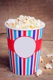 Popcorn στο φλυτζάνι εγγράφου στην ξύλινη επιφάνεια διάστημα αντιγράφων Στοκ εικόνα με δικαίωμα ελεύθερης χρήσης