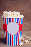Popcorn στο φλυτζάνι εγγράφου στην ξύλινη επιφάνεια διάστημα αντιγράφων Στοκ εικόνες με δικαίωμα ελεύθερης χρήσης