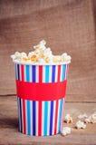 Popcorn στο φλυτζάνι εγγράφου στην ξύλινη επιφάνεια Στοκ φωτογραφίες με δικαίωμα ελεύθερης χρήσης