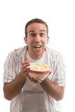 Popcorn. A young man holding a bowl of popcorn and watching a movie, isolated against a white background Royalty Free Stock Image