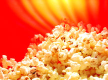Popcorn. Butter popcorn in the oven on warm red background Stock Photography