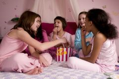 Popcorn. 5 girls at a slumber party enjoying a bucket of popcorn royalty free stock photography