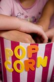 Popcorn. Girls at a slumber party reaching into a bucket of popcorn stock photography
