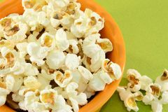 Popcorn. In orange bowl on a green background Royalty Free Stock Photo