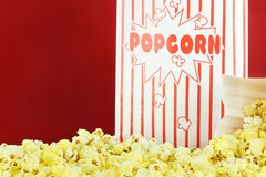 Popcorn. Bags of buttery popcorn against a red background. Room for text stock photography
