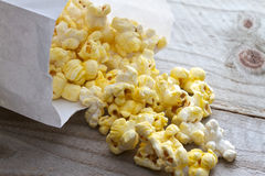 Popcorn. Spilling from plain white bag onto picnic table Royalty Free Stock Image
