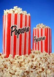 Popcorn. Two bags of popcorn on a blue background royalty free stock photo