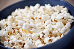 Popcorn. Fresh, buttery popcorn in a blue bowl Royalty Free Stock Image