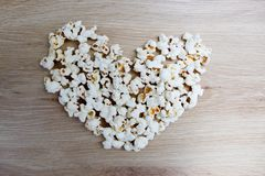 Popcorn arranged in a heart shape on wooden royalty free stock photography