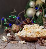 Popcorn on the background of Christmas and New Year`s decorations, selective focus. Popcorn in a wooden bowl on the background of Christmas and New Year`s Stock Photography