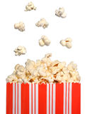 Popcorn bag. A background of a popcorn bag with some popcorn jumping out of the bag, isolated on a white background royalty free stock photo
