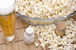 Popcorn and beer. Popcorn, salt, toothpicks and beer om a white background royalty free stock photography