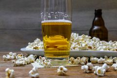 Popcorn and beer on wooden table royalty free stock photography