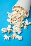 Popcorn bianco sparso da un secchio di Libro Bianco su un fondo blu fotografia stock libera da diritti