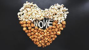 Popcorn on black background. Watching a movie with popcorn. Copy space. Pop corn. Top view. Flat lay. Wooden letters movie with hearts royalty free stock photos