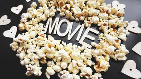 Popcorn on black background. Watching a movie with popcorn. Copy space. Pop corn. Top view. Flat lay. Wooden letters movie with hearts stock images