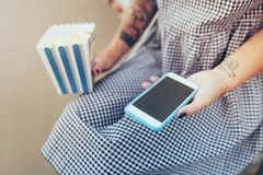 Popcorn  in blue box  and phone in hands with tattoo of girl with gray checkered dress.  stock images