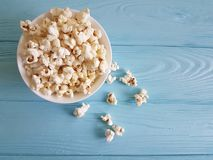 Popcorn closeup on a blue wooden background nutrition traditional cup space for text. Popcorn on a blue wooden background with cup  space for text traditional Royalty Free Stock Images