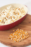 Popcorn in a bowl and corn on a wooden board Stock Photos