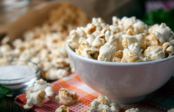 Popcorn into a bowl on a napkin in the kitchen. Salted popcorn into a bowl on a napkin close up stock photography