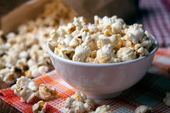 Popcorn into a bowl on a napkin in the kitchen. Salted popcorn into a bowl on a napkin close up royalty free stock photos