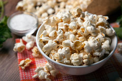Popcorn into a bowl on a napkin in the kitchen Royalty Free Stock Image