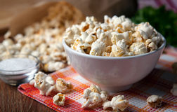 Popcorn into a bowl on a napkin in the kitchen. Salted popcorn into a bowl on a napkin close up royalty free stock image