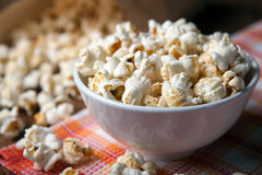 Popcorn into a bowl on a napkin in the kitchen. Salted popcorn into a bowl on a napkin close up royalty free stock photo