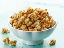 Popcorn. Bowl of sweet caramel popcorn on blue wooden background stock photo
