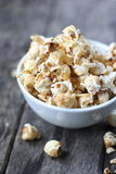 Popcorn in bowl with wooden background Stock Images