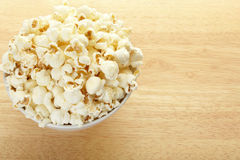 Popcorn bowl on wooden table Stock Image