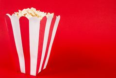 Box of popcorn on red background and space for text royalty free stock photo