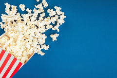 Popcorn. Box of popcorn spilled on blue background Stock Images