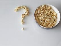 Popcorn breitete in Form einer Frage über einen weißen Hintergrund aus stockbilder