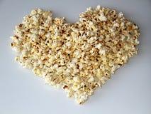 Popcorn breitete in Form eines Herzens auf einem weißen Hintergrund aus stockbild
