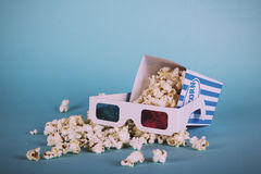 Popcorn bucket against a blue background Vintage Retro Filter. Royalty Free Stock Image