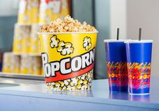 Popcorn Bucket With Drinks On Concession Counter. Popcorn bucket with cold drinks on concession counter at cinema stock photography