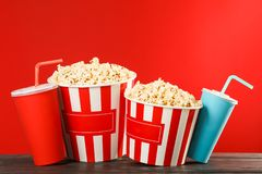 Popcorn buckets and paper cups against red background