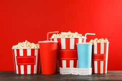 Popcorn buckets, paper cups and tickets against red background