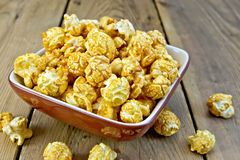 Popcorn caramel on board in clay bowl Royalty Free Stock Photo